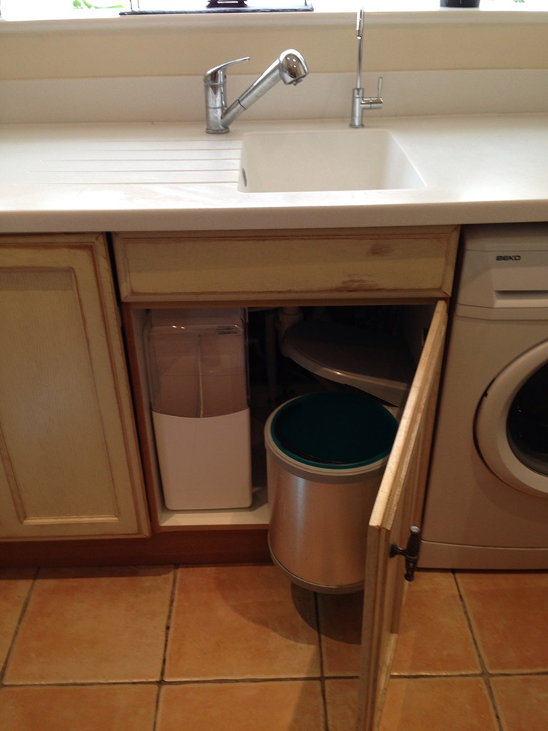 Water softener installed next to a bin in a tight cupboard