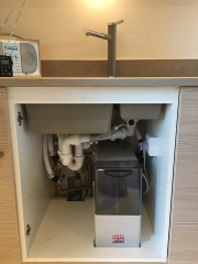 A water softener installed under a sink by removing the cupboard floor