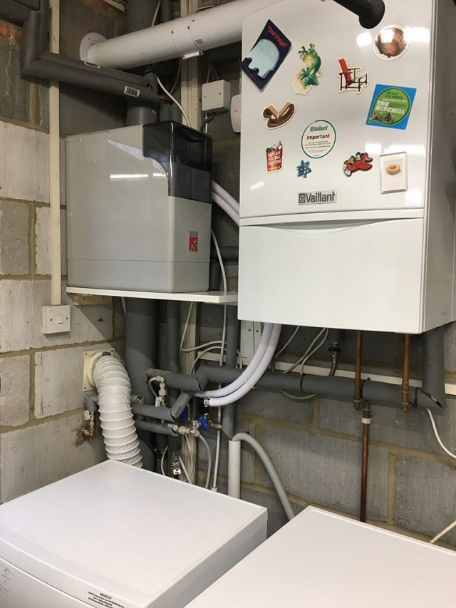 Water softener installed on a shelf in a utility room